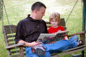 Far og sønn som leser en bok sammen