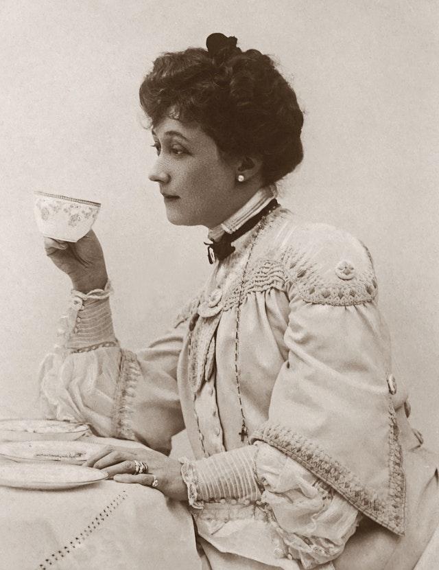 Viktoriansk kledd kvinne som drikker te
