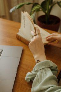 Kvinnehånd som blar i en bok.